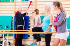 Pensionärer i terapi för fysisk rehabilitering royaltyfri foto