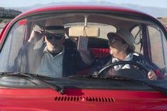 Pensionärer kopplar ihop körning och att ha av gyckel inom en gammal röd bil Royaltyfri Bild