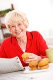 Pensionärer: Kvinna som har en muffin och en tidning Royaltyfri Fotografi