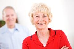 Pensionärer: Kvinna som ser kameran med mannen bakom Royaltyfria Bilder