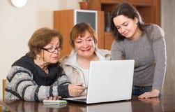 Pensionärer och släkting med bärbara datorn Fotografering för Bildbyråer