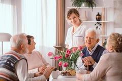 pensionärer på avgånghemmet som talar under ett eftermiddagmellanmål royaltyfri bild