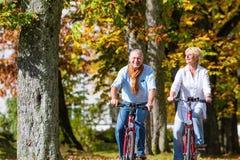 Pensionärer på cyklar som har, turnerar parkerar in Arkivbild