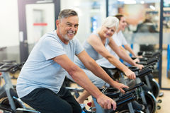 Pensionärer på motionscykeler i snurrgrupp på idrottshallen arkivfoto