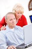 Pensionärer: Par som är förvirrade vid datorproblem Royaltyfri Bild