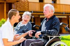 Pensionärer som äter godisen i trädgård av vårdhemmet Royaltyfri Fotografi