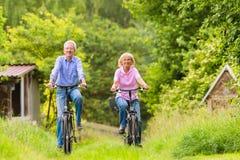 Pensionärer som övar med cykeln Arkivbilder