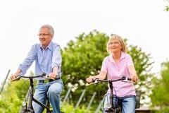 Pensionärer som övar med cykeln royaltyfria foton