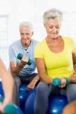 Pensionärer som använder övningsbollen och vikter Arkivbilder