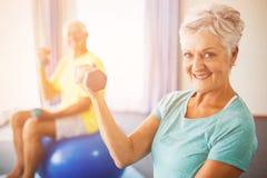 Pensionärer som använder övningsbollen och vikter Royaltyfria Foton