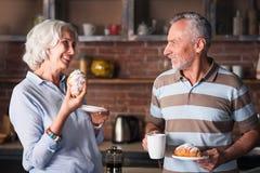 Pensionärer som har kaffe, och cruassan tillsammans i köket Royaltyfri Foto