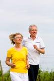 Pensionärer som joggar göra sporten Arkivbild