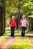 Pensionärer som joggar på en skogväg Arkivbilder
