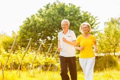 Pensionärer som kör i naturen som gör sporten Royaltyfri Foto