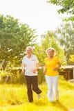 Pensionärer som kör i naturen som gör sporten Arkivfoto