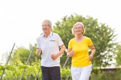 Pensionärer som kör i naturen som gör sporten Arkivfoton