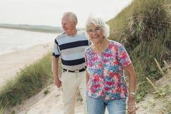 Pensionärer som kopplar av på stranden Arkivbilder