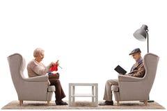 Pensionärer som placeras i fåtöljer med ett av dem handarbete och oten Arkivfoto