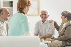Pensionärer som sitter med sjuksköterskan fotografering för bildbyråer