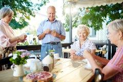 Pensionärer som spelar kort i kafé arkivbild