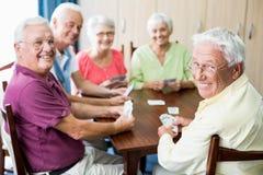Pensionärer som spelar kort tillsammans Arkivfoton