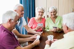 Pensionärer som spelar kort tillsammans royaltyfri foto