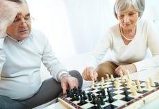 Pensionärer som spelar schack Arkivfoto