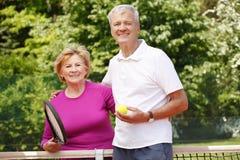 Pensionärer som spelar tennis Arkivfoto