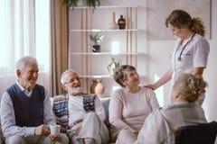 Pensionärer som talar med sjuksköterskan i avgånghemmet royaltyfri foto