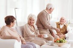 Pensionärer som talar och dricker kaffe Royaltyfri Foto
