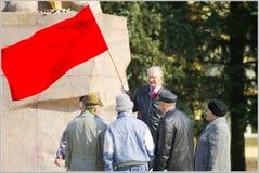 Pensionärer som till varandra talar under röd flagga Arkivfoto