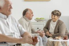 Pensionärer som tycker om gemensam konversation royaltyfria bilder