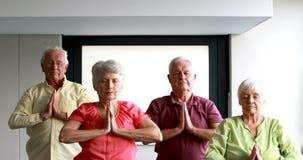 Pensionärer som utför yoga lager videofilmer