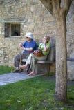 Pensionärer som vilar och gör mobiltelefonappell på Plazaborgmästare, i Ainsa, Huesca, Spanien i Pyrenees berg, ett gammalt, wall Arkivfoto
