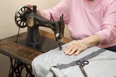 Pensionärer syr kläder på en gammal symaskin Royaltyfri Fotografi