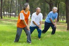 Pensionärer värmer upp, innan de joggar fotografering för bildbyråer