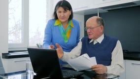 Pensionärfamiljeföretag, den gamla kvinnan svär med makesammanträde bak bärbara datorn med dokument arkivfilmer