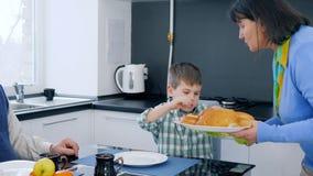 Pensionärfamiljfrunch, mormor kom med läckert bröd på maträtten för unge- och farfarsammanträde på tabellen lager videofilmer