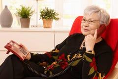Pensionärfrau, die Überlandleitungtelefon verwendet Lizenzfreie Stockbilder
