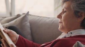 Pensionärfrau, die interessantes Buch in ihren Händen hält stock video footage