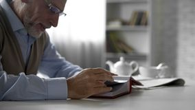 Pensionärgentleman som ser bilder i fotoalbum, lyckliga minnen, nostalgi arkivfoto