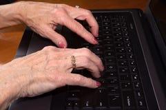 Pensionärhänder på tangentbordet Arkivbilder