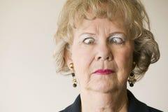 pensionärkvinna för korsade ögon arkivbild