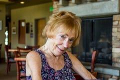 Pensionärkvinna som ser blyg Royaltyfri Fotografi