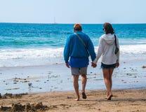 Pensionärperson född under en baby boomman och kvinnliga caucasian par som går på stranden in mot havet som rymmer händer arkivbilder