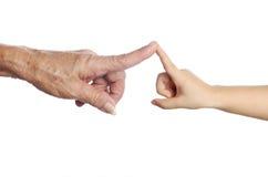 Pensionärs hand som trycker på ett barns hand Royaltyfri Bild