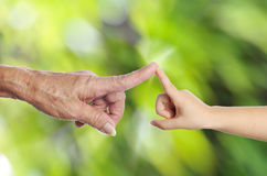 Pensionärs hand som trycker på ett barns hand Arkivfoto