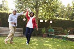 Pensionärsvartpar dansar i deras tillbaka trädgård, full längd royaltyfria foton