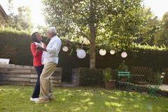 Pensionärsvartpar dansar i deras tillbaka trädgård, full längd royaltyfria bilder