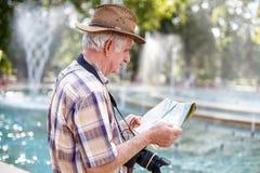 Pensionärtourist im Hut, der nach Bestimmungsort auf Karte in der Gleichheit sucht Lizenzfreies Stockbild